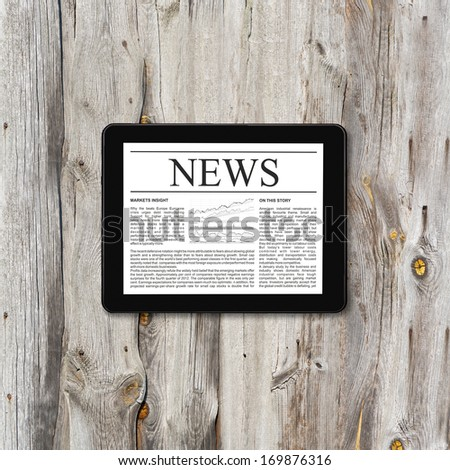 Tablet computer with business news on a screen on a background of wood - stock photo