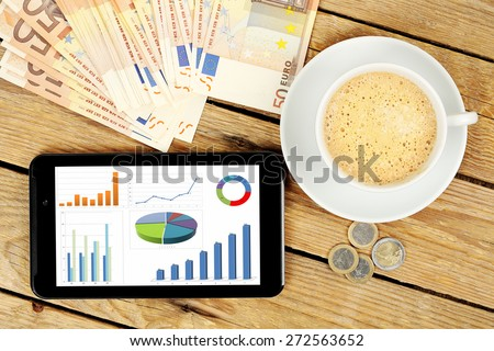 tablet computer with graphs on rustic desk, making money concept - stock photo