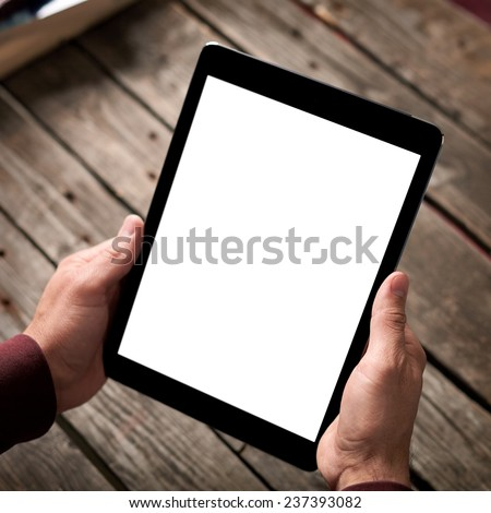 Tablet computer with isolated screen in male hands over table background.