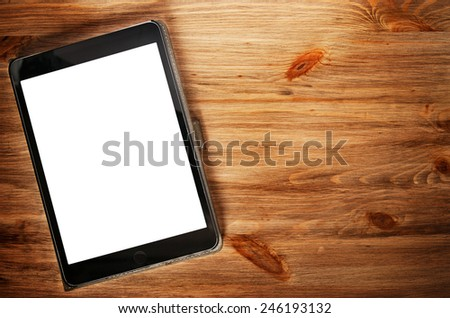 Tablet computer with isolated screen on wooden desk - stock photo