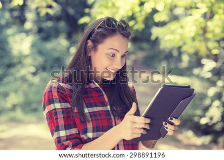 Tablet computer woman excited looking at touch pad pc. Cheerful happy funny Caucasian female model using mobile pc outdoors in park on summer day - stock photo