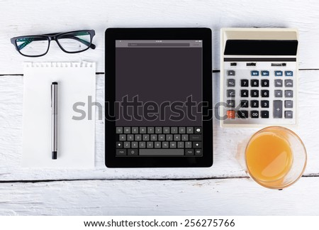 tablet glasses pen note paper calculator  with keyboard on screen on wood backgound - stock photo
