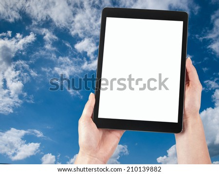tablet hand held against the sky - stock photo