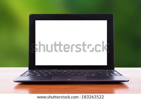Tablet laptop with white blank screen on wooden table, front view, green natural background. - stock photo