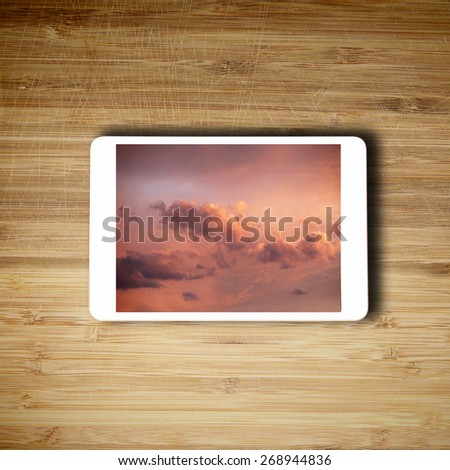 Tablet lying on the table with clouds on the screen - stock photo