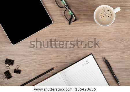 Tablet, notepad, glasses and coffee cup on office wooden table - stock photo