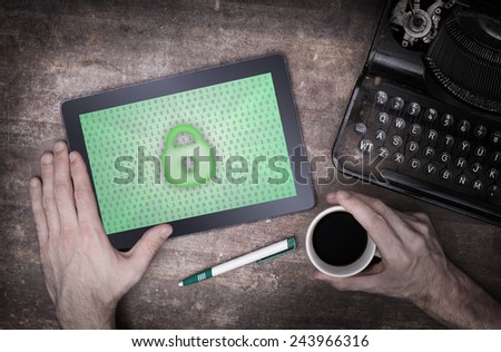 Tablet on a desk, concept of data protection, green - stock photo