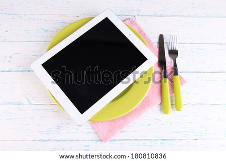 Tablet on plate with fork and knife on wooden background - stock photo