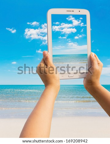 Tablet on the beach Thailand trip - stock photo