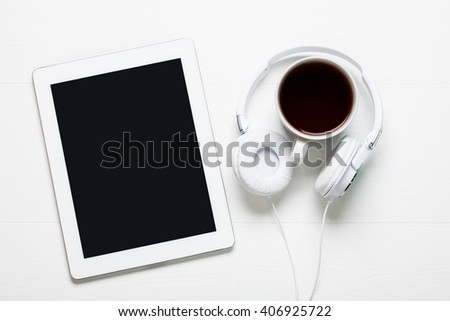 Tablet on white wood with headphone and cup of tea or coffee
