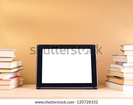 tablet pc and stack book on wooden table - stock photo