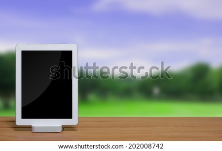 tablet pc computer with dock station on blur park background. - stock photo