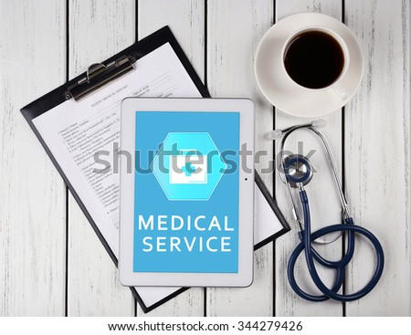 Tablet-pc on doctor table, concept of medical service - stock photo