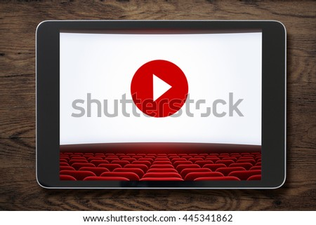 Tablet pc on wooden table with cinema screen displayed. On-line cinema concept.