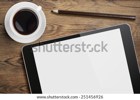 Tablet pc or ipad on table desk with coffee cup and pencil - stock photo