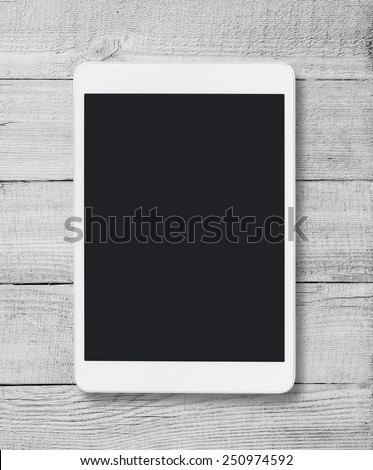 Tablet pc similar to ipad on wood table background - stock photo