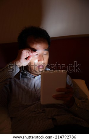 Tablet pc will hurt your eyes in the dark - business man look tablet pc late at night before sleep in the living room, asian - stock photo