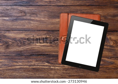 tablet pc with blank screen and brown case on wooden background, top view - stock photo