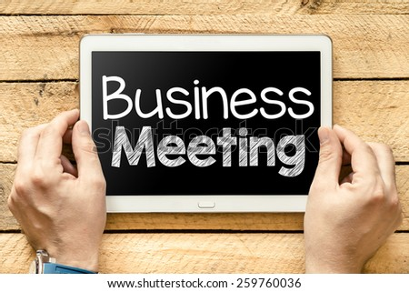 Tablet pc with business meeting. Male hands holding tablet pc with business meeting on wooden background - stock photo