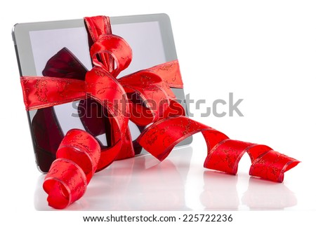 Tablet pc with christmas red ribbon on white background - stock photo