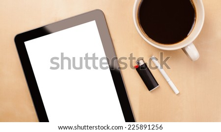 Tablet pc with copy space and a cup of coffee on a wooden work table close-up - stock photo