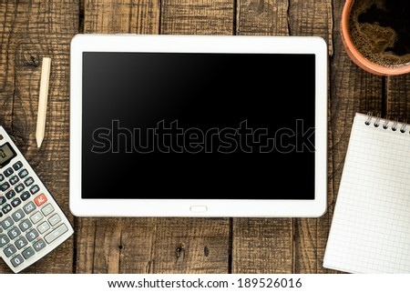 Tablet pc with empty screen and accounting stuff on wooden background - stock photo