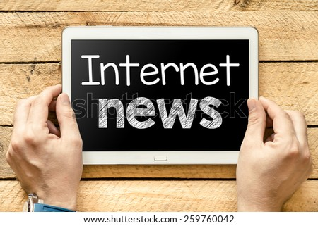 Tablet pc with internet news. Male hands holding tablet pc with internet news on wooden background - stock photo