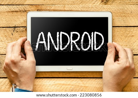 "Tablet PC with text ""Android"". ands hold tablet PC with text ""Android"" over wooden table  - stock photo"