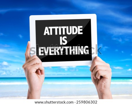 Tablet pc with text Attitude is Everything with beach background - stock photo