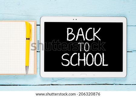 """Tablet pc with text """"back to school""""with notepad and pen on blue wooden background - stock photo"""