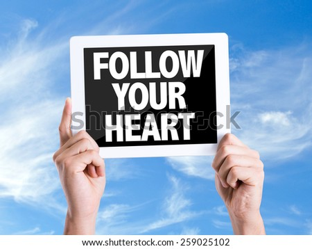 Tablet pc with text Follow Your Heart with sky background - stock photo