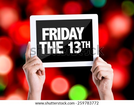 Tablet pc with text Friday The 13th with bokeh background  - stock photo