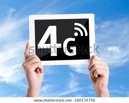 Tablet pc with text 4G with sky background - stock photo
