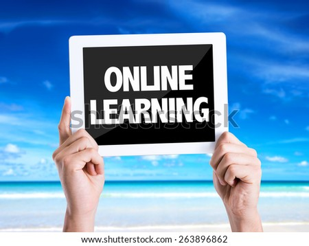 Tablet pc with text Online Learning with beach background - stock photo