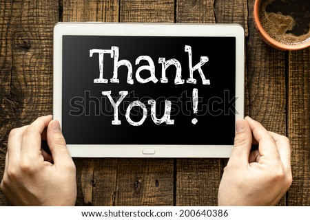 """Tablet pc with text """"Thank You"""" which holding man - stock photo"""