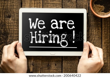 "Tablet pc with text ""We're hiring"" which holding man - stock photo"