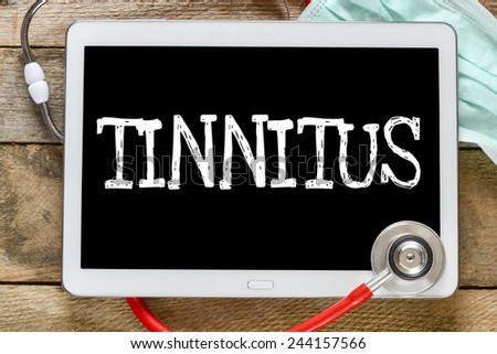 Tablet pc with word Tinnitus. Tablet pc with word Tinnitus and stethoscope, medicine concept - stock photo