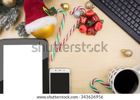 Tablet, smartphone and cup of coffee with winter festive ornaments. - stock photo