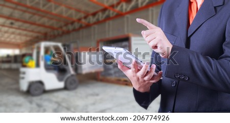 tablet to handle export and import goods prepare the delivery of rubber compactos in warehouse - stock photo