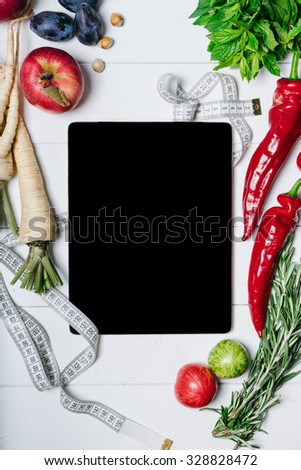 Tablet with a measuring tape, rosemary, parsley root, tomatoes, chili peppers and apples on a white wooden background - stock photo