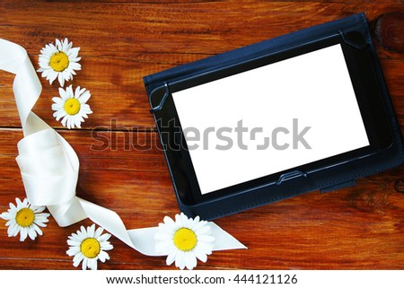 Tablet with a white screen on the wooden background with fresh chamomiles - stock photo