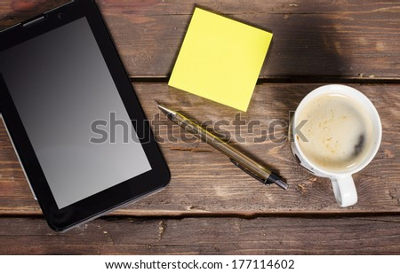 Tablet with blank screen and coffee cup on wooden table - stock photo