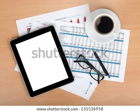 Tablet with blank screen over papers with numbers and charts, coffee cup, glasses and pen. View from above