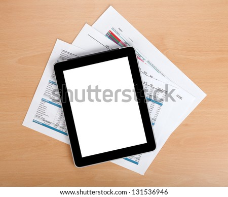 Tablet with blank screen over papers with numbers and charts. View from above - stock photo