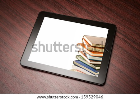 Tablet with book on the table. - stock photo
