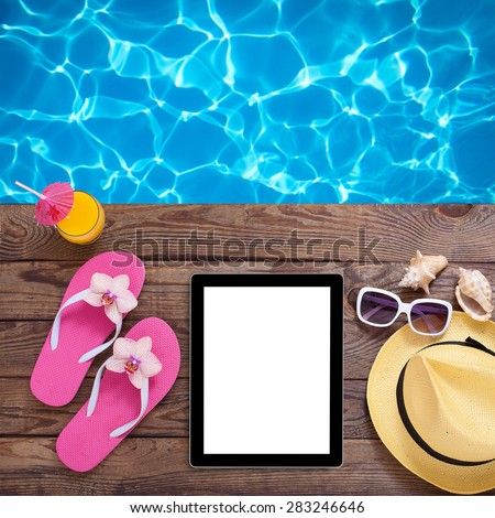 Tablet with clean screen on wooden table. Fashionable clothes sunglasses, hat, flip-flops for beach holiday. Orange juice. Flat mock up for design. Top view. - stock photo