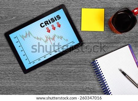 tablet with crisis concept on wooden table - stock photo