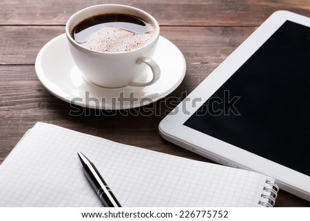 Tablet with dark screen, coffee cup, paper notebook and pen on the wooden table