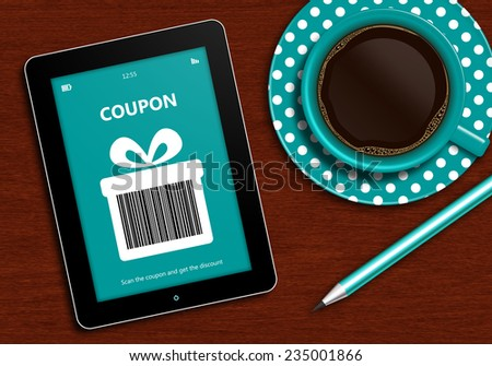 tablet with discount coupon and  cup of coffee lying on wooden desk - stock photo