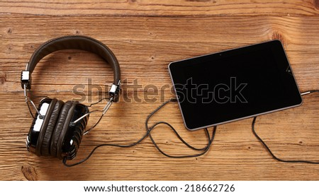 Tablet with headphones on old wooden desk - stock photo